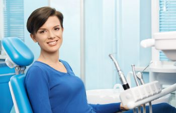 Smiling Woman in a Dental Chair After Cosmetic Dentistry Treatment
