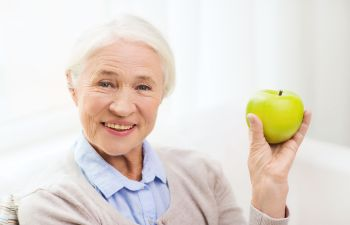 Happy Senior Woman with a Green Apple in Hand