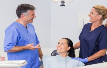 Laughing dentists and a patient in the dentist's office